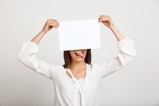 Женщина показывает знак на белой бумаге, сделать объявление