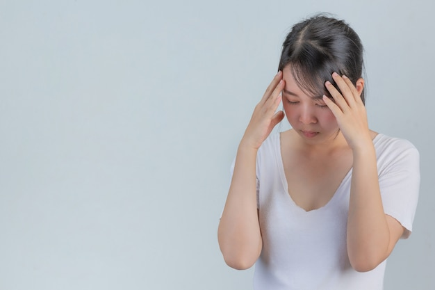Woman showing signs of stress on a gray wall