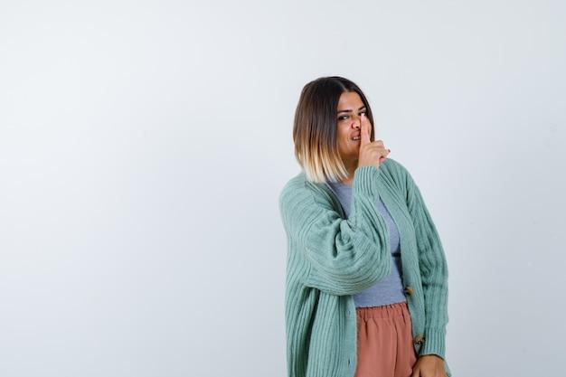 Donna che mostra gesto di silenzio in abiti casual e guardando fiducioso. vista frontale.