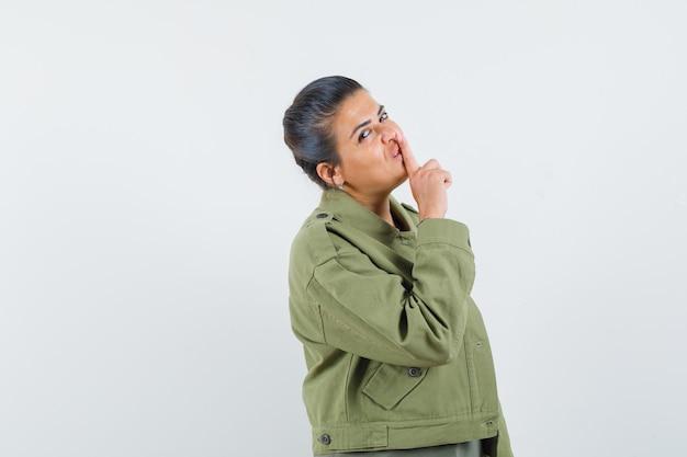 여자 재킷, t- 셔츠에 침묵 제스처를 보여주는 자신감을 찾고.
