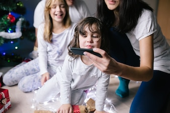 Woman showing smartphone to daughter
