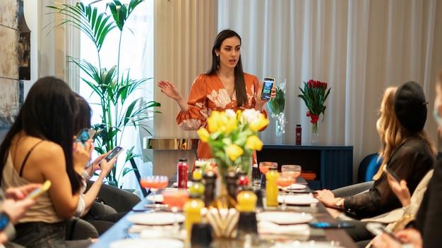 Женщина показывает производство контента социальных сетей на своем смартфоне на мастер-классе.