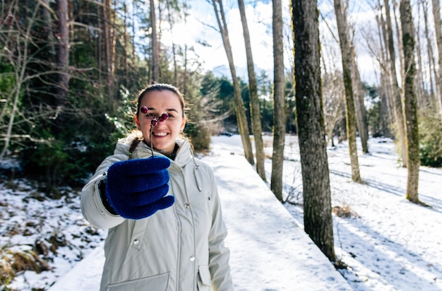 눈 덮인 풍경에 카메라에 몇 가지 열매를 보여주는 여자.