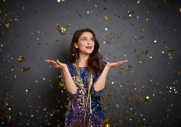 Woman showing something on her hand under shower of confetti