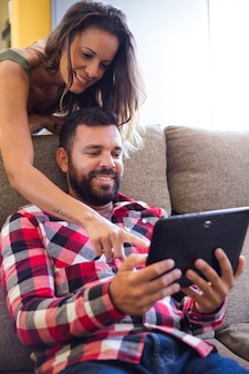Woman showing something to her husband on digital tablet screen