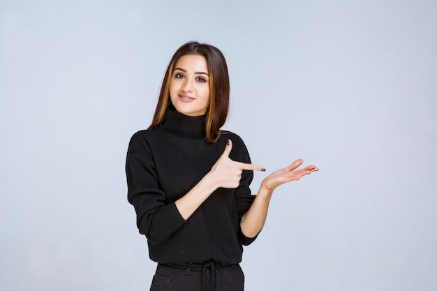 Женщина показывает что-то в руке.