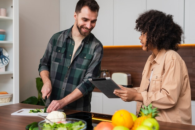 Woman showing something on tablet to man cooking