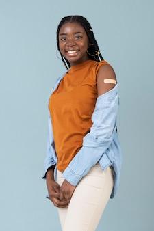 ワクチン接種後に腕にステッカーを示す女性