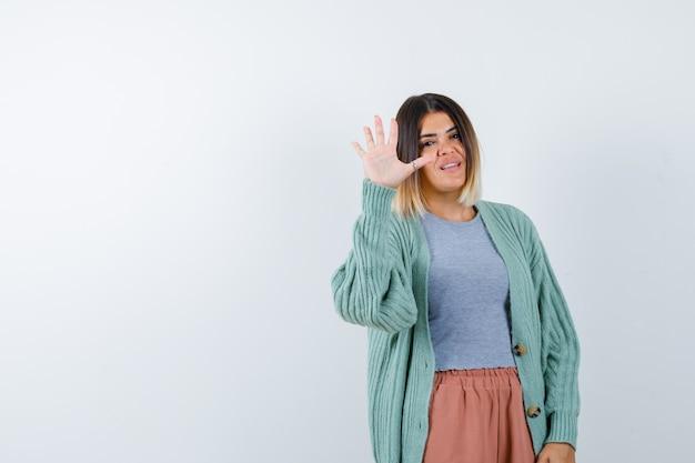 Donna che mostra il gesto di arresto in abiti casual e guardando fiducioso, vista frontale.