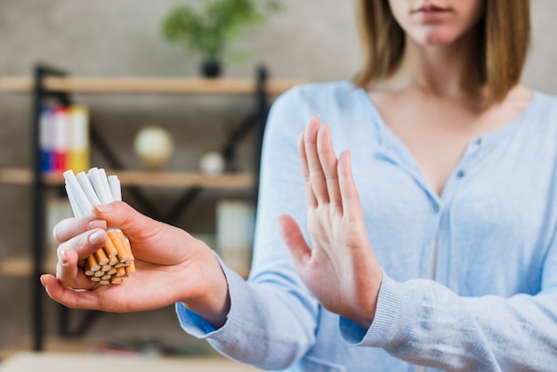 Woman showing stop gesture holding bunch of cigarettes in hand