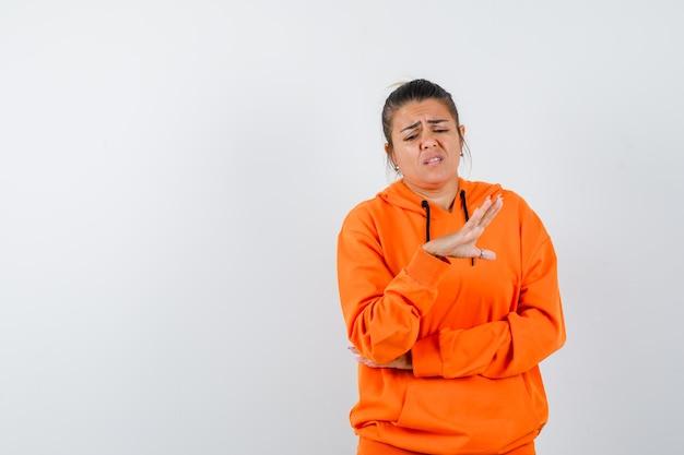 Женщина показывает жест стоп в оранжевой толстовке с капюшоном и выглядит недовольной