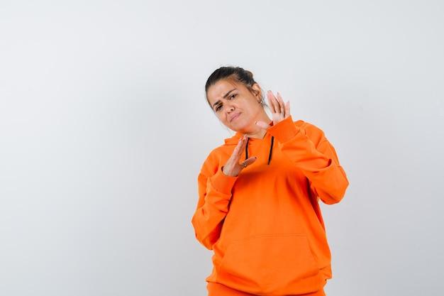オレンジ色のパーカーで停止ジェスチャーを示し、怖がって見える女性