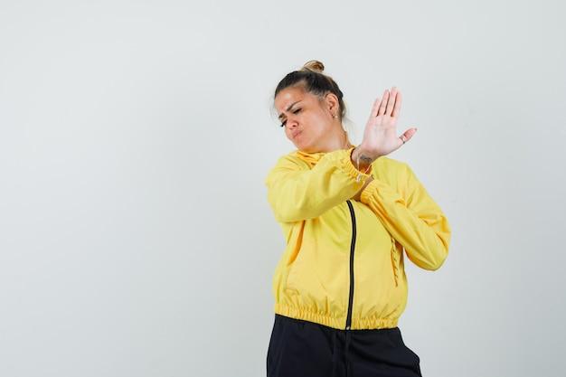 Женщина показывает жест остановки в спортивном костюме и выглядит раздраженным. передний план.