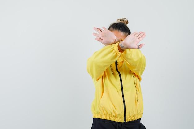 Женщина показывает жест остановки в спортивном костюме и выглядит раздраженной, вид спереди.