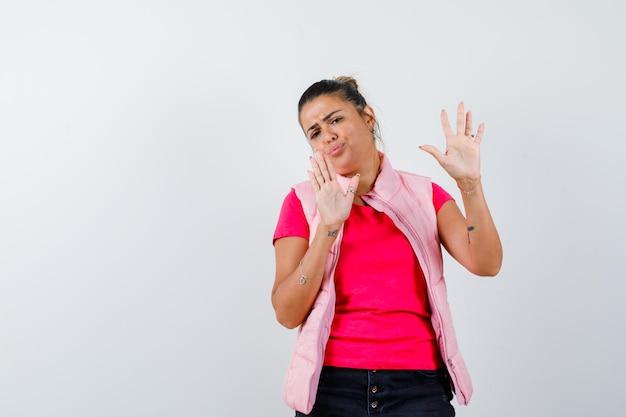 Женщина показывает жест остановки в футболке, жилете и выглядит раздраженной