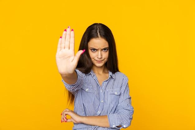 Женщина показывает стоп, стоя на желтом