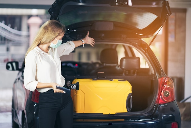 Woman showing suitcase in car trunk