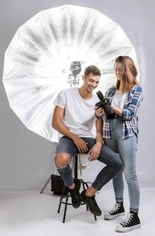 Женщина показывает фотографии на камеру для модели