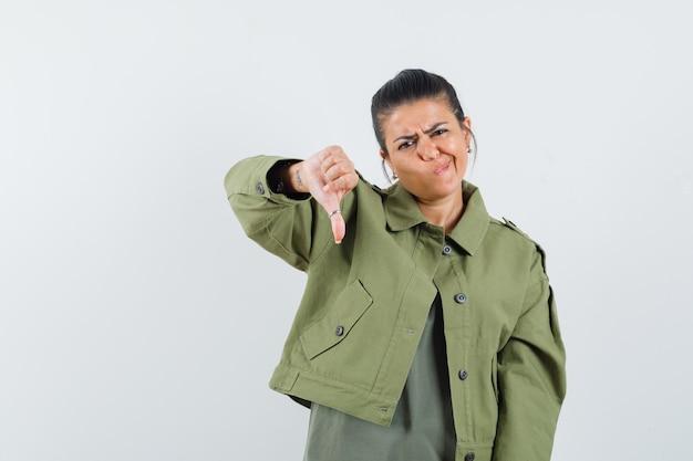 재킷, t- 셔츠에 아래로 엄지 손가락을 보여주는 여자 잠겨있는 찾고