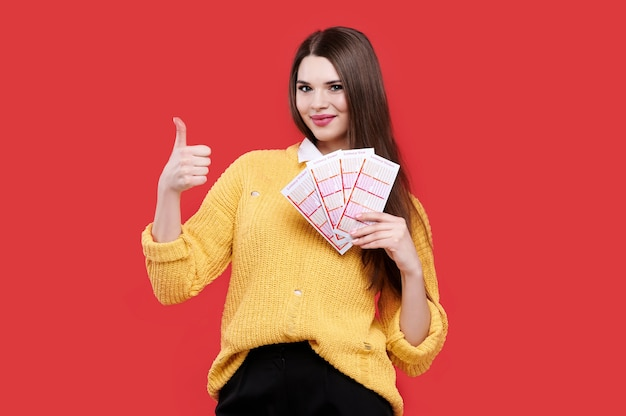 Woman showing thumb up gesture and holding lottery tickets