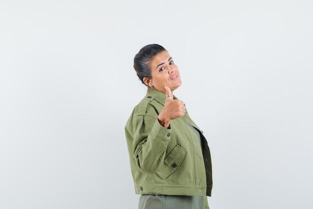ジャケット、tシャツに親指を立てて自信を持って見える女性。