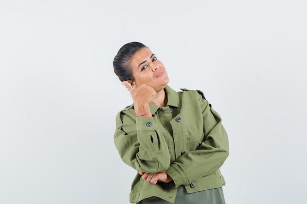 Женщина показывает палец вверх в куртке, футболке и выглядит довольной