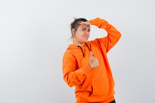 Donna che mostra pollice in su, guardando la telecamera con la mano sopra la testa in felpa con cappuccio arancione e sembra carina