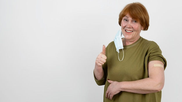 Woman showing thumbs up and bandage on arm after vaccine shot
