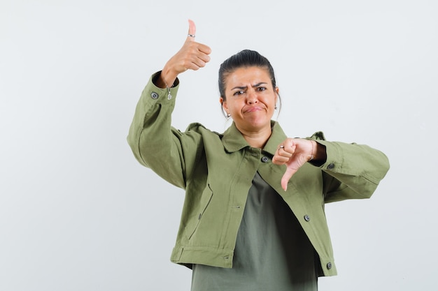 Woman showing thumbs up and down in jacket, t-shirt and looking hesitant