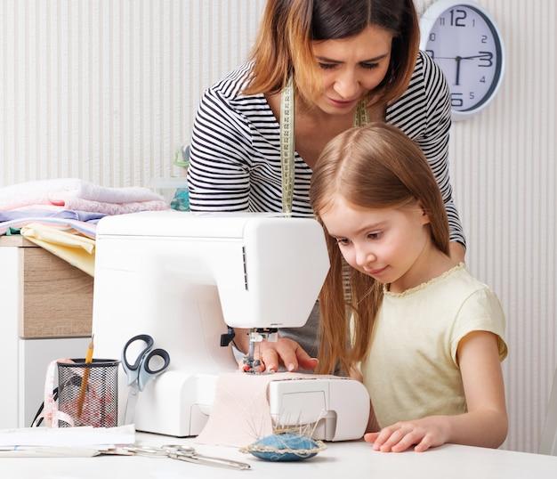 女性が自宅で縫う方法を子供に示す