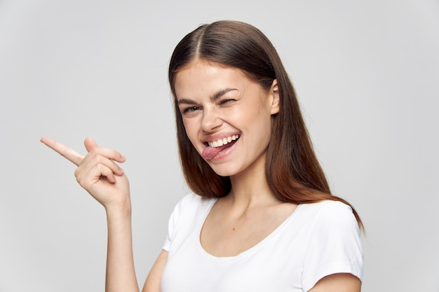 Woman showing tongue and finger to the side over isolated background fun laugh copy space