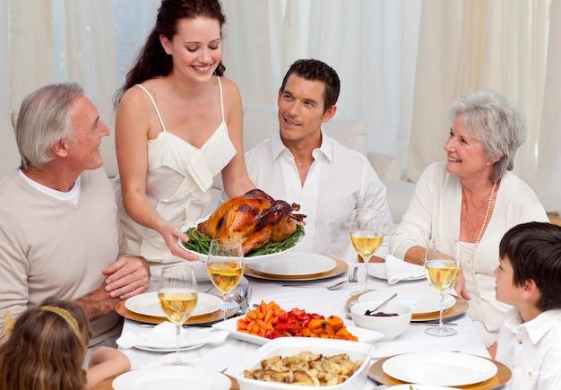 크리스마스 저녁 식사에 대 한 그녀의 가족에 게 터키를 보여주는 여자