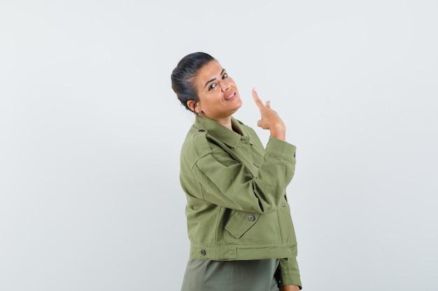 Vサインインジャケット、tシャツを見せて元気そうな女性。