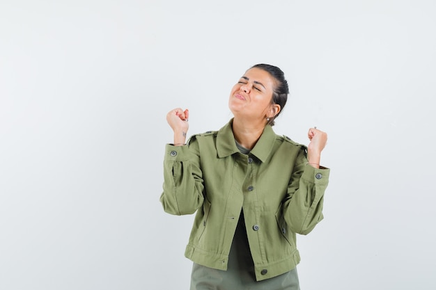 Woman showing winner gesture in jacket, t-shirt and looking lucky.
