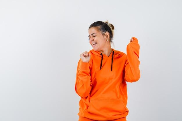 Woman showing winner gesture in orange hoodie and looking happy