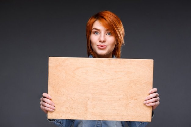 Woman showing wooden board on grey wall