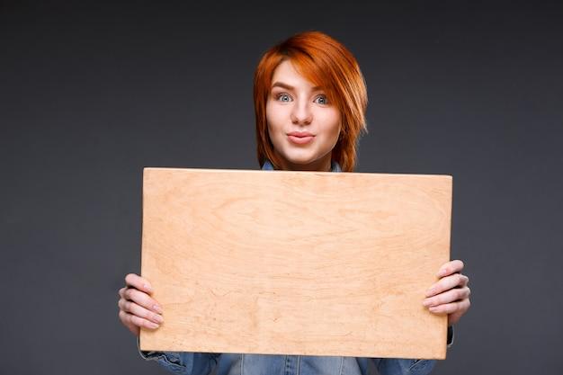 회색 벽에 나무 보드를 보여주는 여자