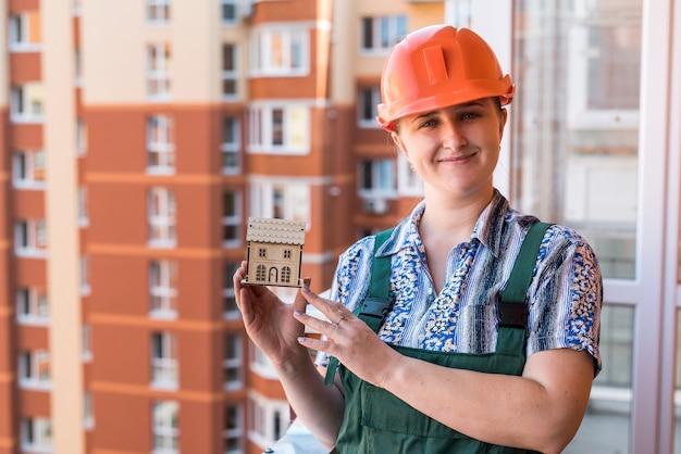 발코니에 목조 주택 모델을 보여주는 여자