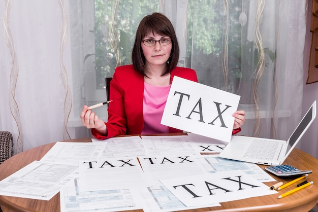 종이에 단어 '세금'을 보여주는 여자