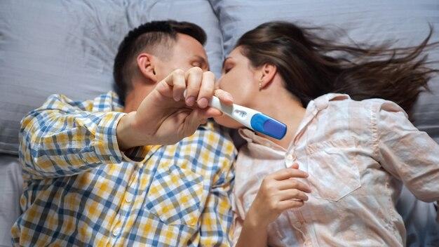 女性は男性にベッドに横たわっている妊娠検査、上面図、幸福を示しています