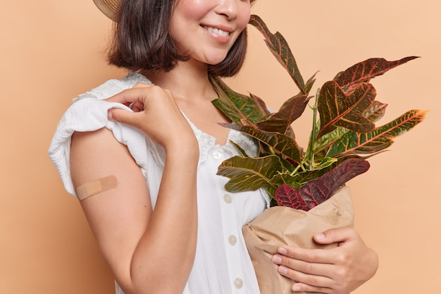 Woman shows adhesive plaster on arm after getting inoculation promots vaccination campaign holds potted domestic plant poses on brown