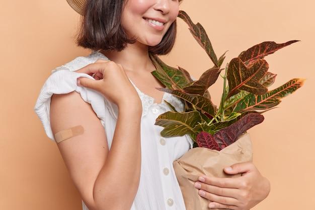 Женщина показывает лейкопластырь на руке после прививки, пропагандирует кампанию вакцинации, держит позы домашних растений в горшках на коричневом