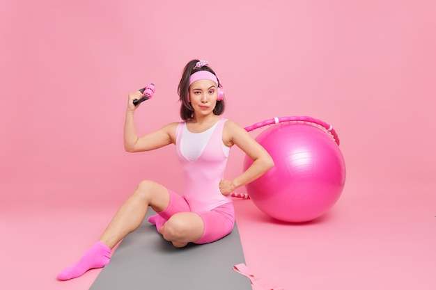 Woman shows biceps raises arm trains muscles with sport equipment goes in for sport regularly sits on fitness mat listens music via headphones uses swiss ball hula hoop