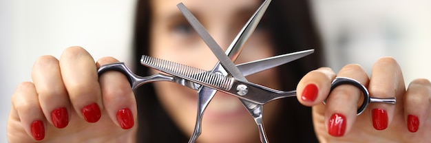 Woman shows classic steel hairdresser tool close-up