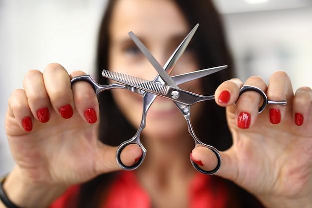 Женщина показывает классический стальной инструмент парикмахера крупным планом