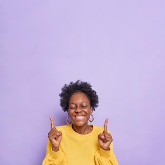 La donna mostra una bella pubblicità gioisce per qualcosa punti in vendita banner o offerte promozionali sorrisi indossa ampiamente un maglione giallo isolato su viola