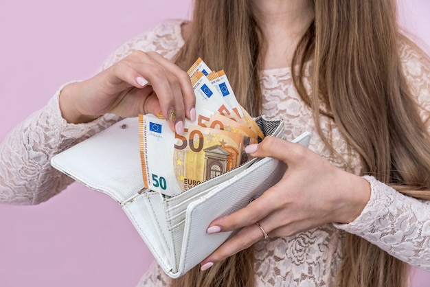 여자는 그녀의 지갑에 유로 지폐를 보여줍니다.