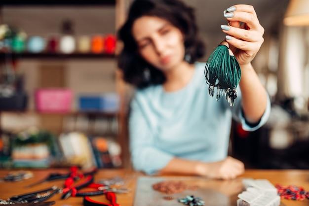 Женщина показывает браслет ручной работы, хобби рукоделия. женский мастер на рабочем месте, инструменты мастеров на столе