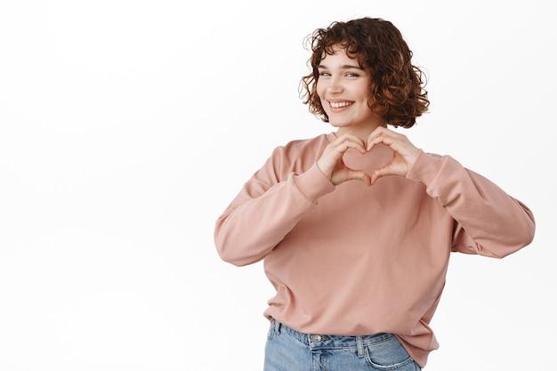 La donna mostra il cuore ti amo firmare, fare complimenti, esprimere simpatia o simili, in piedi su bianco