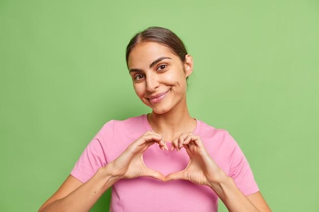 여자는 녹색에 캐주얼한 분홍색 티셔츠를 입은 부드럽게 미소 짓는 당신과 그녀의 감정을 공유하는 마음 사랑 제스처를 보여줍니다